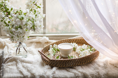 Fotografija Fresh Spring blossom with a cup of coffee near window with raindrops where sheer