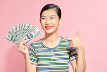 Photo Of Rich Woman In Basic Clothing Holding Fan Of Dollar Money Isolated Over Pink Background
