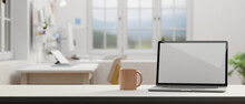 Laptop With Mock-up Screen And Coffee Mug On The Table In Comfortable Office Room, 3D Rendering