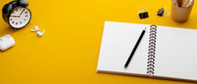 Yellow Study Table With Stationery, Clips, Earphones And Clock, 3D Rendering