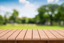 Empty Old Wooden Table In Front Of Blurred View Of Lawn, Big Tree, Blue Sky And Sunshine Background Of Nature With Copy Space. Can Be Used For Display Or Montage For Show Your Products.