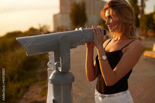Stampa su Tela Woman using binoculars on observation deck