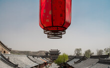 """A Red Lantern Above Chinese Old House Roof. The Text On The Lantern Means """"good Luck""""."""