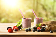 Forest Berry Yogurt Smoothie In Glass On Table In Forest