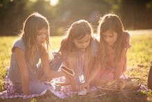 Three Little Girls Having Picnic In Nature.