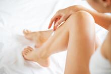Woman Applying Body Lotion On Her Leg
