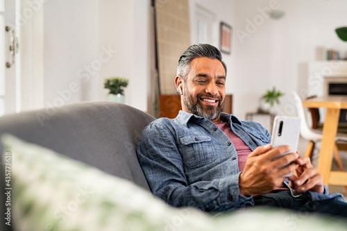 Fototapeta Happy mature man using smartphone while listening to music