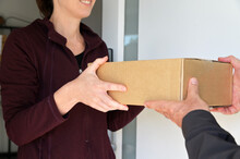 Woman Receiving A Package From A Currier