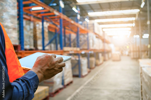 Fotografiet The  man holding tablet to checking the stock products,Employee using warehouse software to checking the stock of products in the warehouse,spot focus hand hold tablet