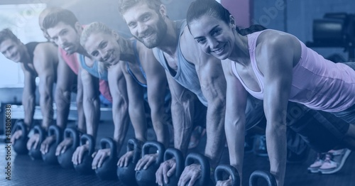 Composition of fit smiling men and women doing push ups on kettlebells in gym