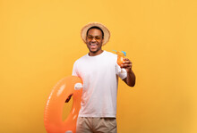Joyful Black Man With Tasty Summer Cocktail Holding Inflatable Ring, Going To Beach Party On Yellow Studio Background