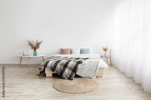 Bed with pillows and blanket, round carpet, tables with dry plants in vases on wooden floor