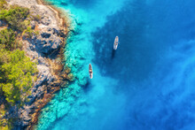 Aerial View Of People On Floating Sup Boards On Blue Sea, Rocks, Trees At Sunset In Summer. Blue Lagoon, Oludeniz, Turkey. Tropical Landscape. Kayaks On Clear Water. Active Travel. Top View Of Canoe