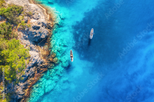 Fotografía Aerial view of people on floating sup boards on blue sea, rocks, trees at sunset in summer