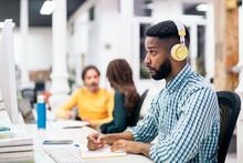 African Office Worker Wearing Headphones