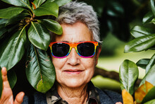 Horizontal Portrait Of Older Lady From The Lgbt Community Smiling With Sunglasses Among Green Plants. Lesbian Granny. Other Sexualities Concept