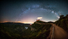 Panoramic Of The Milky Way Over A Medieval Castle On A Lake. Beautiful Views Of The Milky Way Above A Castle On A Mountain Hill Surrounded By A Large Lake