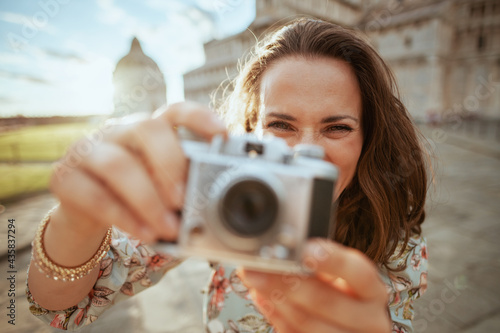 Fotografie, Obraz stylish solo traveller woman in floral dress with film camera