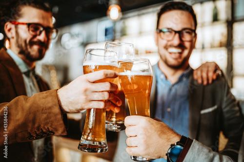 Foto Business people drink beer after work in pub