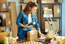 Happy Female In Jeans Using Phone Applications In Warehouse