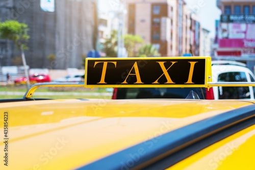 Fotografie, Obraz Word TAXI on roof of yellow cab at city street in summer day.