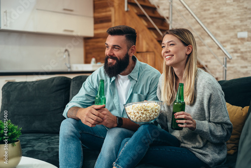 Couple drinking beer and eating popcorn at home while watching television Fototapet