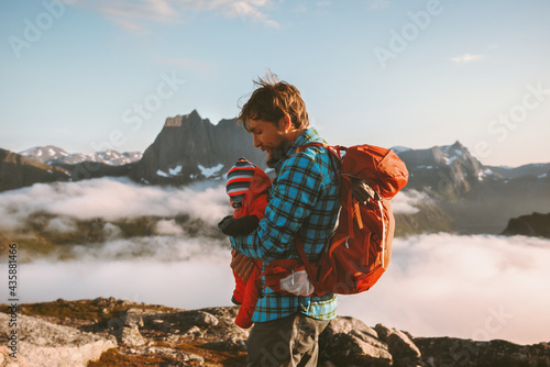 Fotografie, Obraz Father hiking with baby in mountains family vacations outdoor in Norway adventur