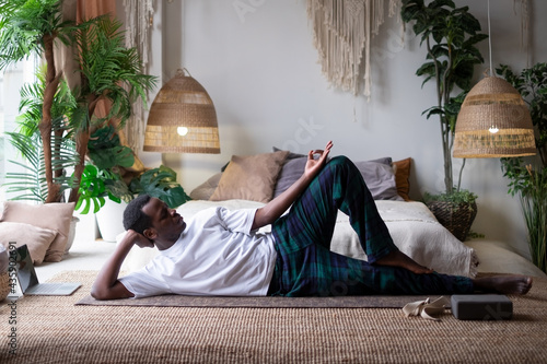Foto African yoga man doing anantasana pose working out at home