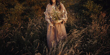 Beautiful Woman In Linen Dress Gathering Wildflowers In Summer Meadow In Evening. Stylish Young Female In Rustic Dress Picking Flowers In Countryside. Atmospheric Stylish Vintage Image