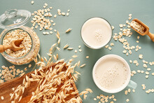 Oat Milk In A Glass And Mug On A Blue Background. Flakes And Ears For Oatmeal And Granola On A Wooden Plate.