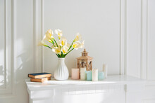 Soft Home Decor, White Jug, Vase With White And Yellow Beautiful Flowers On A White Wall Background And On A Wooden Shelf. Interior.
