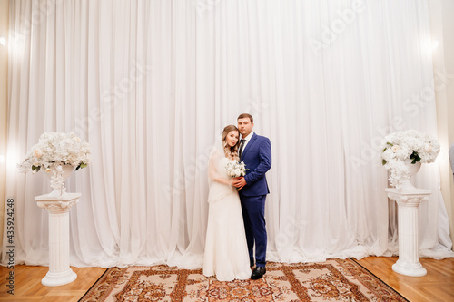 beautiful and happy bride and groom against the background of the white curtain Fotobehang