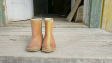 A Small Boots Infront Of The Old Wooden House In Yellow And Red Color