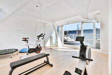 Interior Of Light House Room Furnished With Gym Equipment Of Bench And Cycling Machine