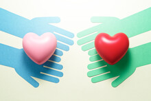 People Helping Each Other. Compassion Relationship Image. Green Hands And Blue Hands Giving Hearts Each Other.