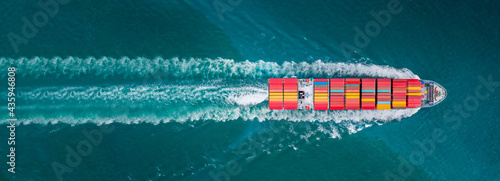 Obraz na plátně Aerial top view of cargo ship with contrail in the ocean sea ship carrying conta