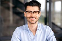 Close Up Portrait Of Handsome Confident Successful Young Caucasian Man Wearing Glasses, Wearing Stylish Shirt, Sitting At Office, Looking Directly At Camera And Smiling Friendly