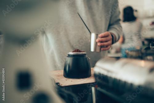 Canvastavla Barista measure coffee powder and brewing black moka coffee using moka coffee maker