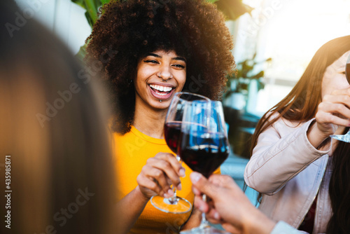 Valokuva Happy african american woman drinking red wine at bar restaurant - Multiracial f