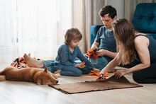 Family Leisure Activity. Happy Family Making Diy Snuffle Mats For Their Domestic Dog And Cat