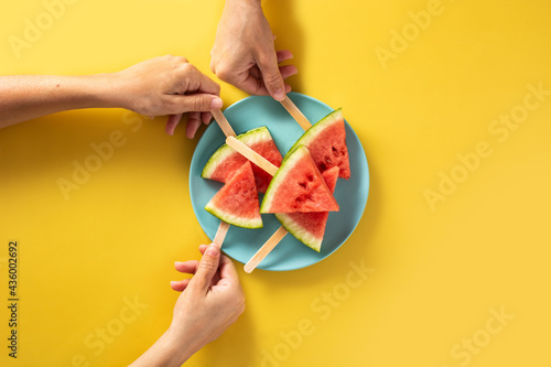 Fototapeta Hand picking up watermelon slices popsicles on blue plate and yellow background