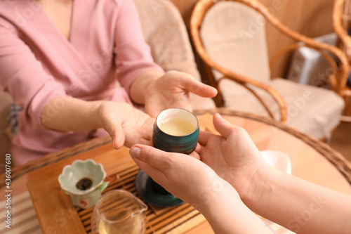 Fotografiet Master giving freshly brewed tea to guest during ceremony at table, closeup