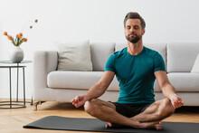 Man With Closed Eyes Meditating In Lotus Pose On Yoga Mat