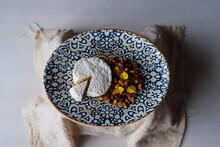 Plano De Un Pequeño Pastel Blanco Cortado Con Nueces Y Flores Comestibles En Un Plato Sobre La Mesa