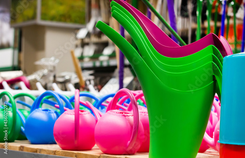 Fotografie, Obraz Photo of various colored watering cans and buckets on store shelf