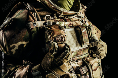 Canvastavla Photo of soldier in level 3 armored vest ammunition, tactical gloves using pouch on black background