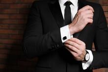Man Wearing Stylish Suit And Cufflinks Near Brick Wall, Closeup