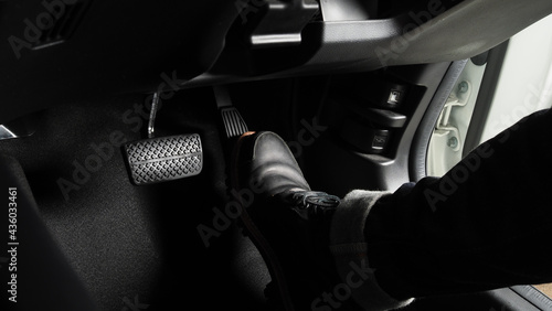 Fotografering Foot pressing foot pedal of a car to drive