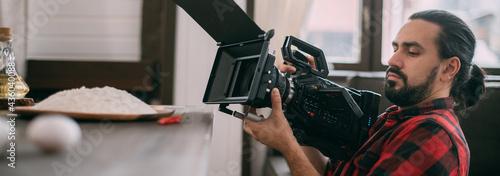 Billede på lærred Director of photography with a camera in his hands on the set.