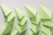 Folded Green Paper Squares Tucked Inside One Another On White